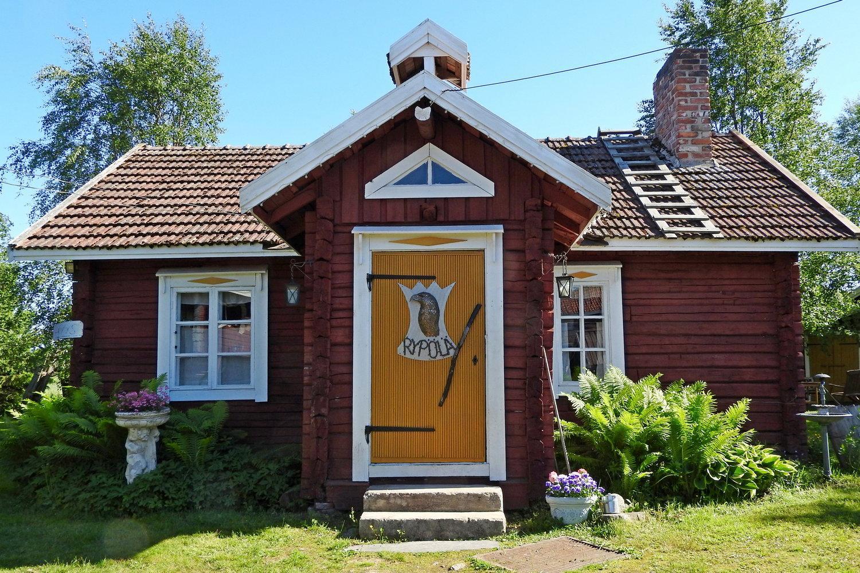 Kesäisessä kuvassa vanha punainen hirsirakennus, edestä päin kuvattuna. Keltainen ovi, jossa torpan nimikyltti.