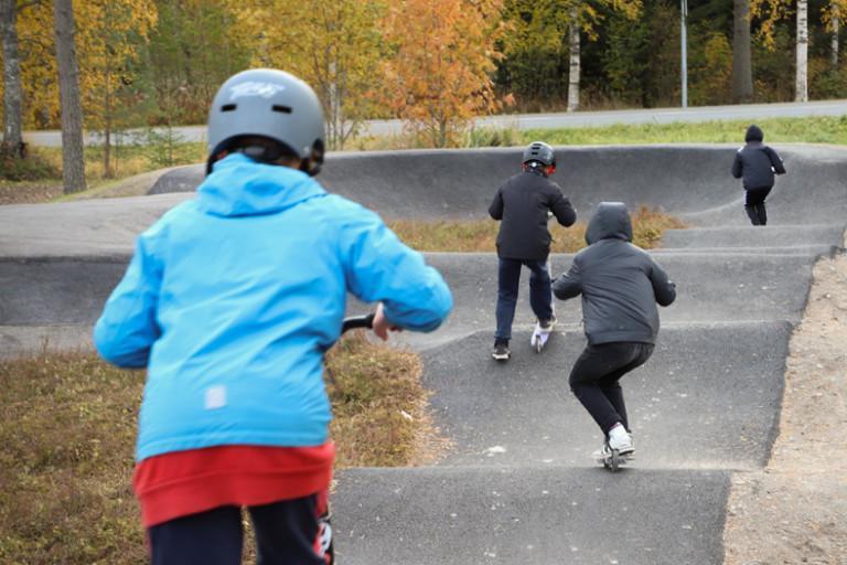 Skeittiparkin radalla on neljä lasta potkulaudoilla selin päin kameraa. Etumaisella lapsella on sininen takki ja punainen paita sekä kypärä päässä, muilla lapsilla on tummat vaatteet.