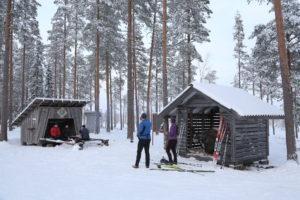 Talvisessa kuvassa on ihmisiä laavulla istumassa, etualalla kaksi seisovaa ihmistä ja suksia.