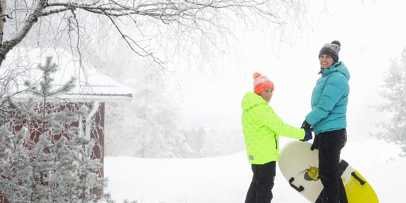 Talvisessa maastossa nainen ja lapsi menossa laskemaan mäkeä, pitävät toisiaan kädestä ja katsovat hymyileen kameraan.