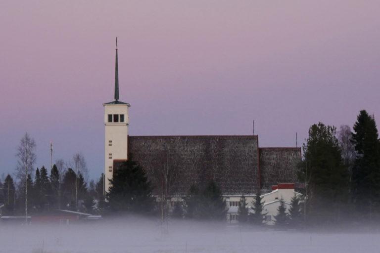 Teuvan kirkko kuvattu sivusta, usvainen talvikuva, taivas on värjäytynyt violetiksi.