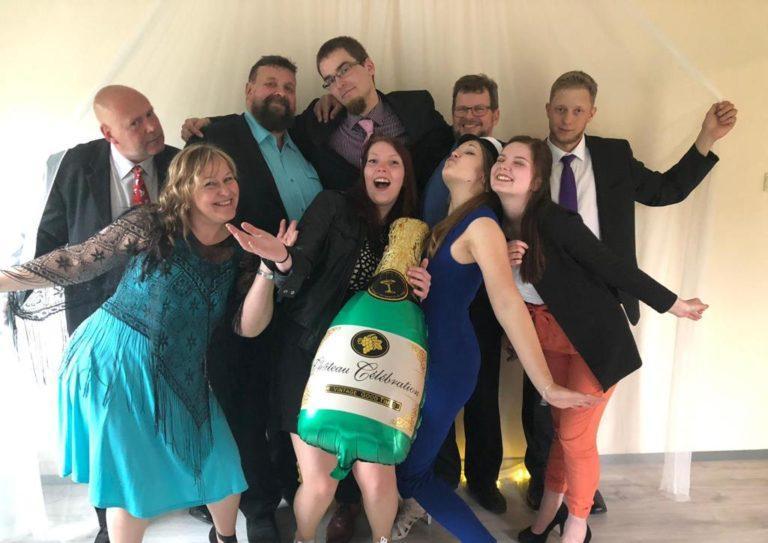 Toukolan näytelmäryhmä, kuvassa yhdeksän henkilöä sekä puhallettava kuohuviinipullo.