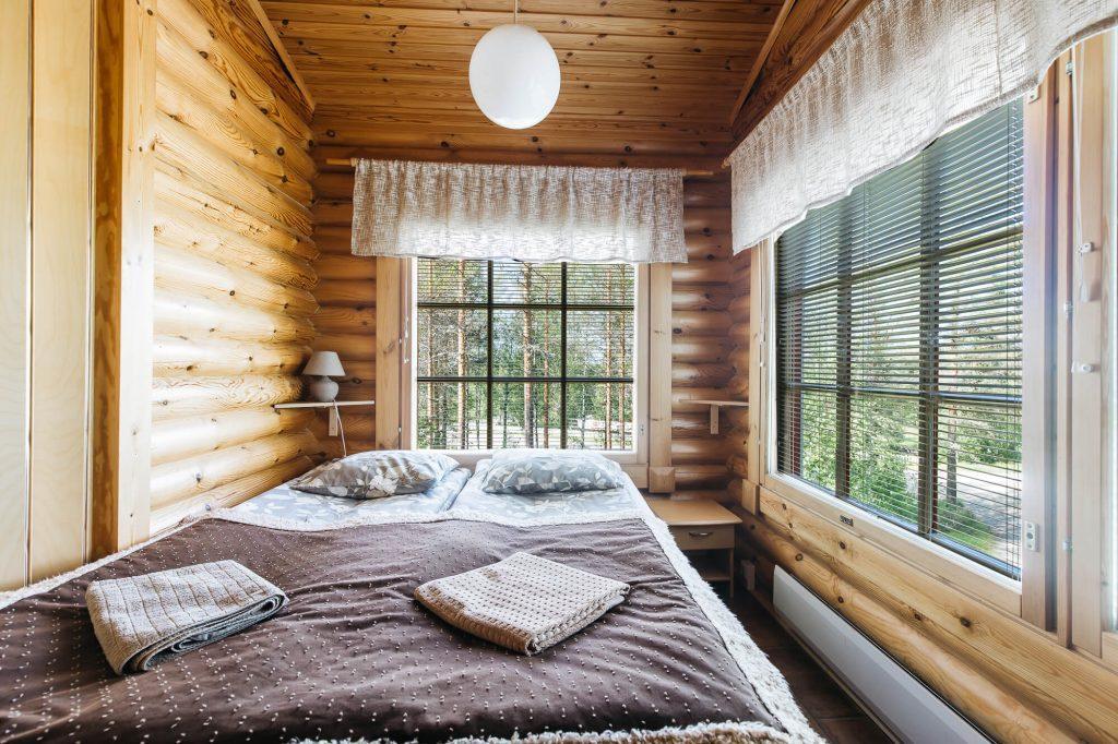 Hirsiseinäine huone, jossa kaksi ikkunaa, sänky ja kattovalo.