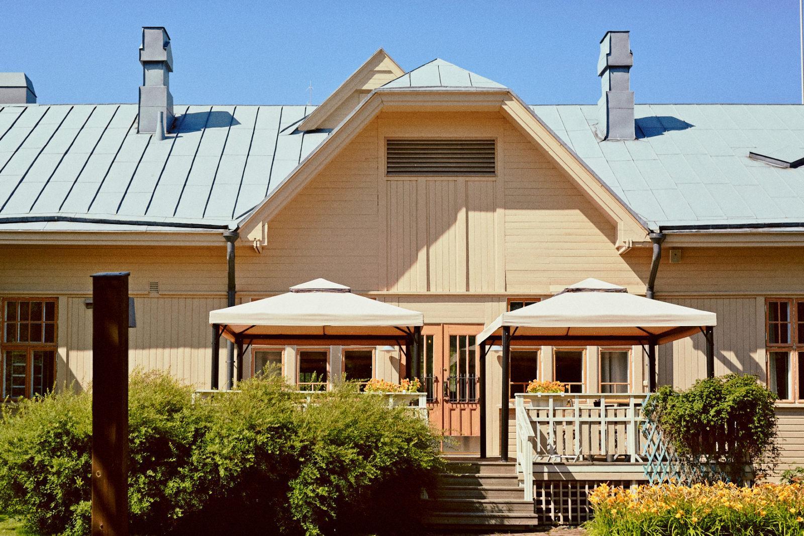 Kesäisessä kuvassa vanha asemarakennus, jossa nykyään toimii Wanha asema niminen lounas- ja tilausravintola.