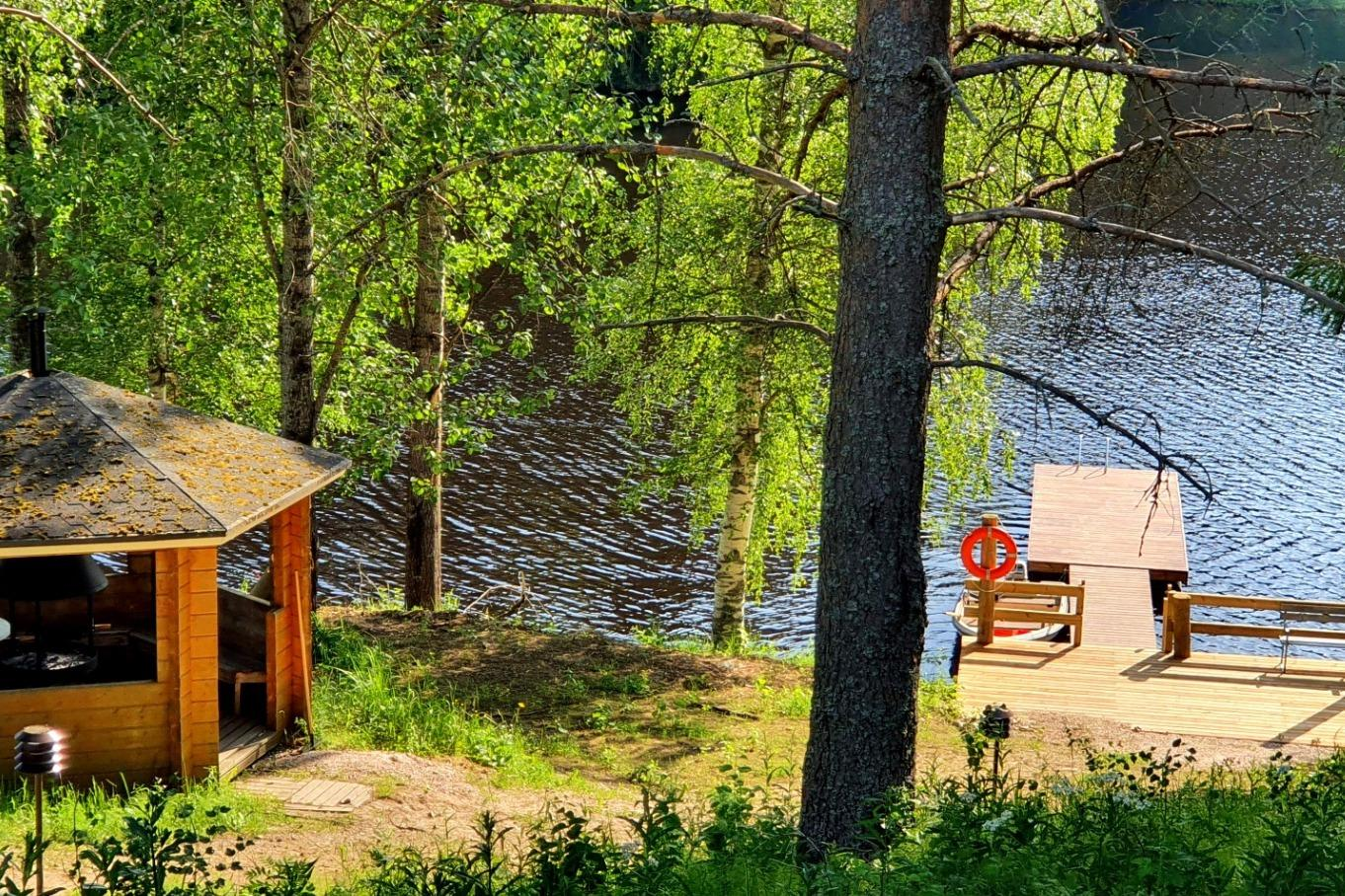 Kesäisessä kuvassa grillikatos sekä laituri järven rannalla.